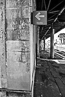 insegna che segnala l'uscita da una stazione delle linee SUD EST. Reportage che racconta le situazioni che si incontrano durante un viaggio lungo le linee ferroviarie SUD EST nel salento.