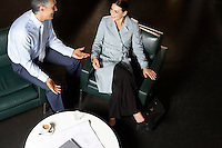 Businessman and businesswoman talking at office table elevated view