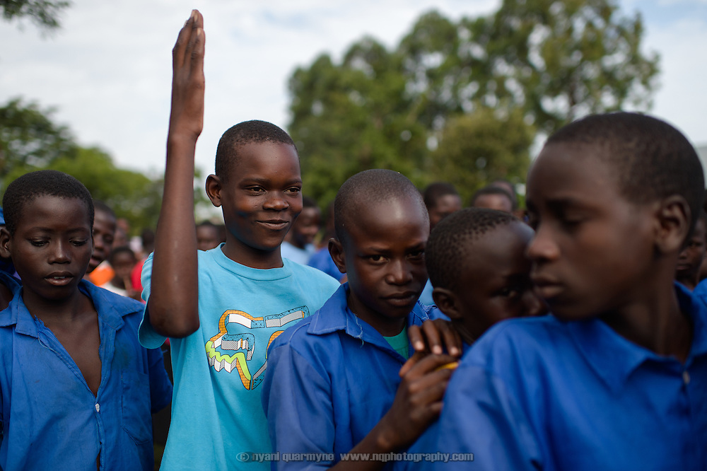 A student raises his hand to answer a question during a presentation on Menstrual Hygiene Management at Agwait Primary School near Tororo in Eastern Uganda on 1 August 2014.