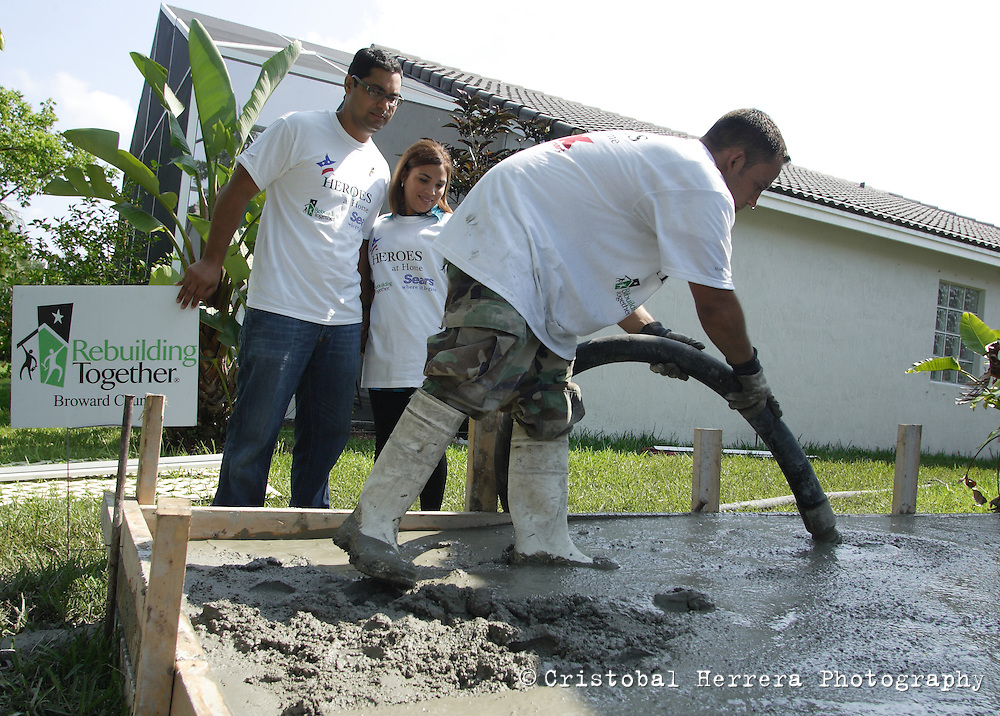 "Hugo Gonzalez, retired US Army Specialist, left, observes, next to his wife Any, a worker making a 12' x 50 concrete patio at his home in Hollywood on Tuesday June 16, 2009. Sears Holdings in support of ""Heroes at Home"" and ""Rebuilding Together Broward County, Inc"" approved a $40,000 grant to make an improvement to Gonzalez home An improvised explosive device injured Gonzalez on June 21, 2004, while serving is the US Army in Iraq. Staff photo/Cristobal Herrera....."