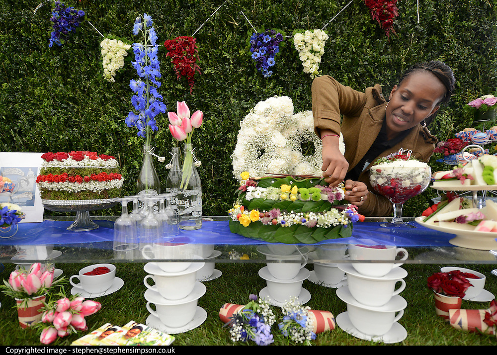 © Licensed to London News Pictures. 21/05/2012. Chelsea, UK. Natalie Howell who is studying at Southwark College puts the finishing touches to the College's Jubilee Street Party Garden. Individual pieces were made by a team of students studying a Diploma in Floristry. Press preview of The Chelsea Flower Show today 21 May 2012. The world's most famous flower show, which has been held in the grounds of the Royal Chelsea Hospital since 1913, will be open to the public from Tuesday. Visitors are expected to flock in their thousands to see displays of plants, flowers and furniture for ideas on how to decorate their gardens.. Photo credit : Stephen Simpson/LNP