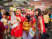 "08 FEBRUARY 2016 - BANGKOK, THAILAND: People pose for ""selfies"" with a Taoist deity during the Chinese New Year parade in Bangkok's Chinatown district during the celebration of the Lunar New Year. Chinese New Year is also called Lunar New Year or Tet (in Vietnamese communities). This year is the ""Year of the Monkey."" Thailand has the largest overseas Chinese population in the world; about 14 percent of Thais are of Chinese ancestry and some Chinese holidays, especially Chinese New Year, are widely celebrated in Thailand.       PHOTO BY JACK KURTZ"