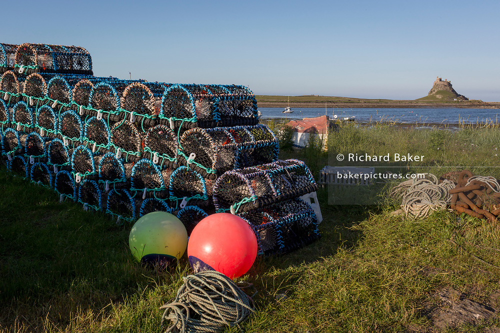 Fishing pots and Lindisfarne Castle on Holy Island, on 27th June 2019, on Lindisfarne Island, Northumberland, England. The Holy Island of Lindisfarne, also known simply as Holy Island, is an island off the northeast coast of England. Holy Island has a recorded history from the 6th century AD; it was an important centre of Celtic and Anglo-saxon Christianity. After the Viking invasions and the Norman conquest of England, a priory was reestablished.