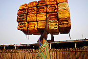 12-01-29  --  ANEHO, TOGO  --  A young woman carries empty jerry cans into a warehouse at the Togo-Benin border filled with hundreds of 240-250 litre barrels of petrol. Smugglers say each barrel is worth $150,000 CFA ($300 USD). Fuel purchased in Nigeria, arrives at this distribution point by boat and is spread throughout Togo, Benin, Burkina Faso and Mali. Photo by Daniel Hayduk