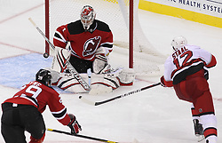 Oct 10; Newark, NJ, USA; New Jersey Devils goalie Johan Hedberg (1) makes a save on Carolina Hurricanes center Eric Staal (12) during the third period at the Prudential Center. The Devils defeated the Hurricanes 4-2.
