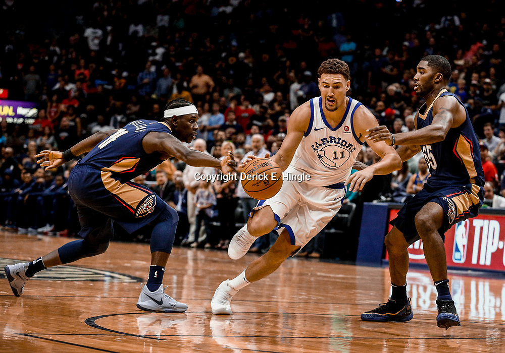 Oct 20, 2017; New Orleans, LA, USA; Golden State Warriors guard Klay Thompson (11) drives past New Orleans Pelicans guard Jrue Holiday (11) and New Orleans Pelicans guard E'Twaun Moore (55) during the first quarter of a game at the Smoothie King Center. Mandatory Credit: Derick E. Hingle-USA TODAY Sports