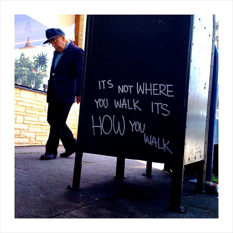 Pedestrian walks past a graffiti-filled mailbox in San Francisco.