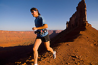 A young woman runs along a ridgeline trail in Castle Valley near Moab, Utah.