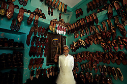 Asia, India, Rajasthan, Jaisalmer.  Shoemaker in shop with colorful embroidered leather shoes