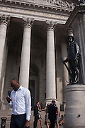 Lunchtime City workers eat lunches beneath the pillars of Royal Exchange during an unusual autumn heatwave on 13th September 2016, in the City of London, England.