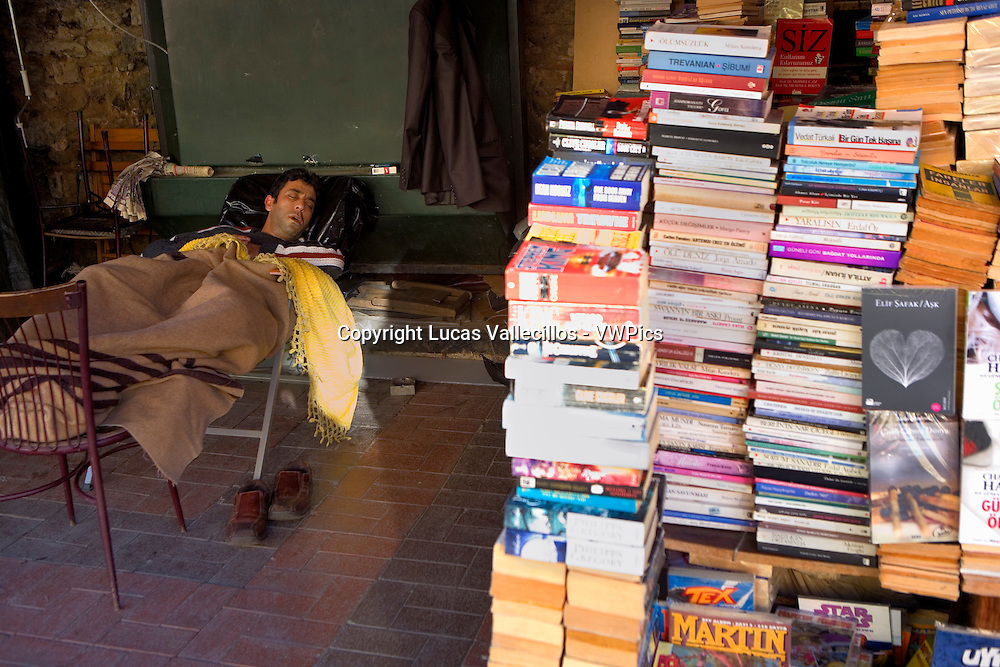 Seller sleeping. Book stall.Book market at Ortakoy Shil Park. At Ortaköy district.  Istanbul. Turkey
