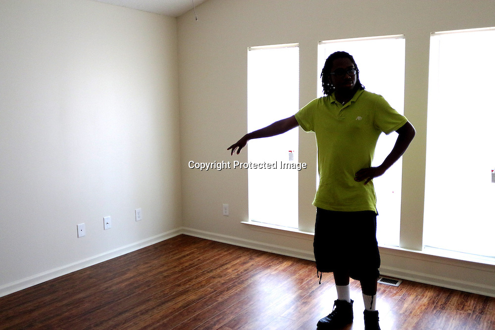 Homeowner Christian Pierce looks through a room in what will be his new home after closing Sunday June 22, 2014 during a Cape Fear Habitat for Humanity dedication ceremony of a recently completed home on Tiffany Drive in Wilmington, N.C. (Jason A. Frizzelle)