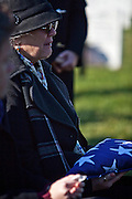 Sharon Frizzell cries as she holds onto the flag that was draped over her husbands casket as he is laid to rest at Arlington National Cemetery on November 8th, 2010.