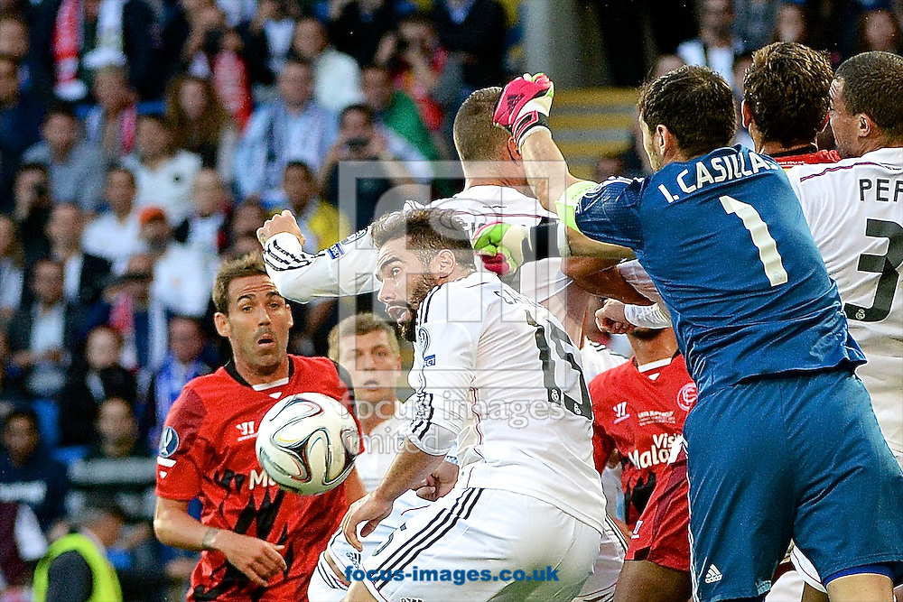 Iker Casillas of Real Madrid punches clear through a crowd of players during the European Super Cup match at the Cardiff City Stadium, Cardiff<br /> Picture by Ian Wadkins/Focus Images Ltd +44 7877 568959<br /> 12/08/2014