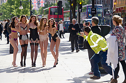 © Licensed to London News Pictures. 16/05/2012. London, UK. Members of the public photograph Models as they pose in Marks & Spencer's new lingerie line in honour of the Queen's jubilee year at photocall outside Marks & Spencer on Oxford Street, London on May 16, 2012. Photo credit : Ben Cawthra/LNP