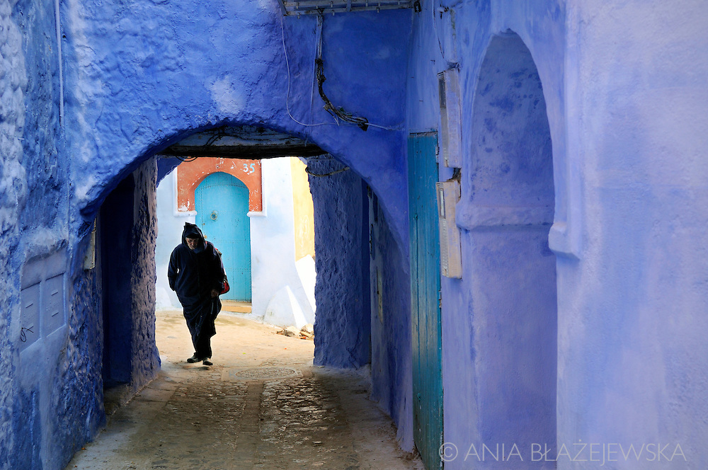 Morocco, Chefchaouen. Man wearing a jellaba in the archway of the blue medina in Chefchaouen.