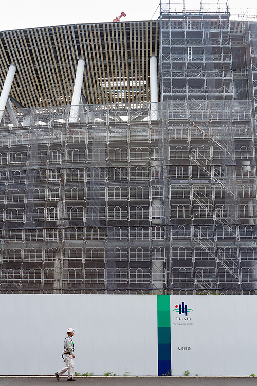 A workmen walks  in front of the construction site for the new main stadium for the 2020 Tokyo Olympics in Gaiemmae, Tokyo, Japan Tuesday June 26th 2018. After many delays the main stadium construction is expected to be finished by November 2019. The Tokyo 2020 Olympics will take place from July 24th to August 9th  2020