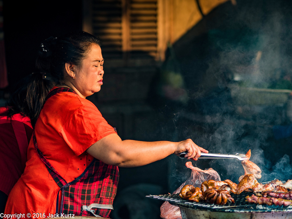"13 MARCH 2016 - LUANG PRABANG, LAOS: A woman grills meat in the market in Luang Prabang. Luang Prabang was named a UNESCO World Heritage Site in 1995. The move saved the city's colonial architecture but the explosion of mass tourism has taken a toll on the city's soul. According to one recent study, a small plot of land that sold for $8,000 three years ago now goes for $120,000. Many longtime residents are selling their homes and moving to small developments around the city. The old homes are then converted to guesthouses, restaurants and spas. The city is famous for the morning ""tak bat,"" or monks' morning alms rounds. Every morning hundreds of Buddhist monks come out before dawn and walk in a silent procession through the city accepting alms from residents. Now, most of the people presenting alms to the monks are tourists, since so many Lao people have moved outside of the city center. About 50,000 people are thought to live in the Luang Prabang area, the city received more than 530,000 tourists in 2014.    PHOTO BY JACK KURTZ"