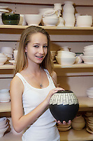 Portrait of a happy teenage girl with vase in workshop