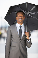 Portrait of a happy African American businessman holding umbrella