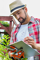Portrait of mature male gardener examining plants growing while writing report on clipboard