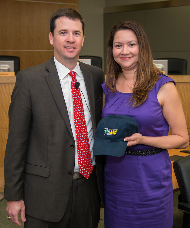 Dr. Andrew Houlihan, left, presents Park Place Elementary School principal Silvia Trinh, right, with a Team HISD cap, June 11, 2014.
