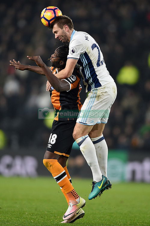 Hull City's Dieumerci Mbokani (left) and West Bromwich Albion's Gareth McAuley (right) battle for the ball in the air during the Premier League match at the KCOM Stadium, Hull.