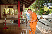 Apr. 3, 2010 - KHUN SAMUTCHINE, THAILAND: A monk at Wat Samutchine works on rebar that will be used to make a sea wall to protect the temple. Rising sea levels brought about by global climate change threaten the future of Khun Samutchine, a tiny fishing village about 90 minutes from Bangkok on the Gulf of Siam. The coastline advances inland here by about 20 metres (65 feet) per year causing families to move and threatening the viability of the village. The only structure in the village that hasn't moved, their Buddhist temple, is completely surrounded by water and more than 2 kilometers from the village. The temple and the village have asked the Thai government and several NGOs for help, but the only help so far is a narrow concrete causeway the government is building that will allow people to walk into the temple from a boat landing two miles away. The walk to the village from a closer boat landing is shorter, but over an unimproved mud flat that is nearly impassible in the rainy season.  PHOTO BY JACK KURTZ