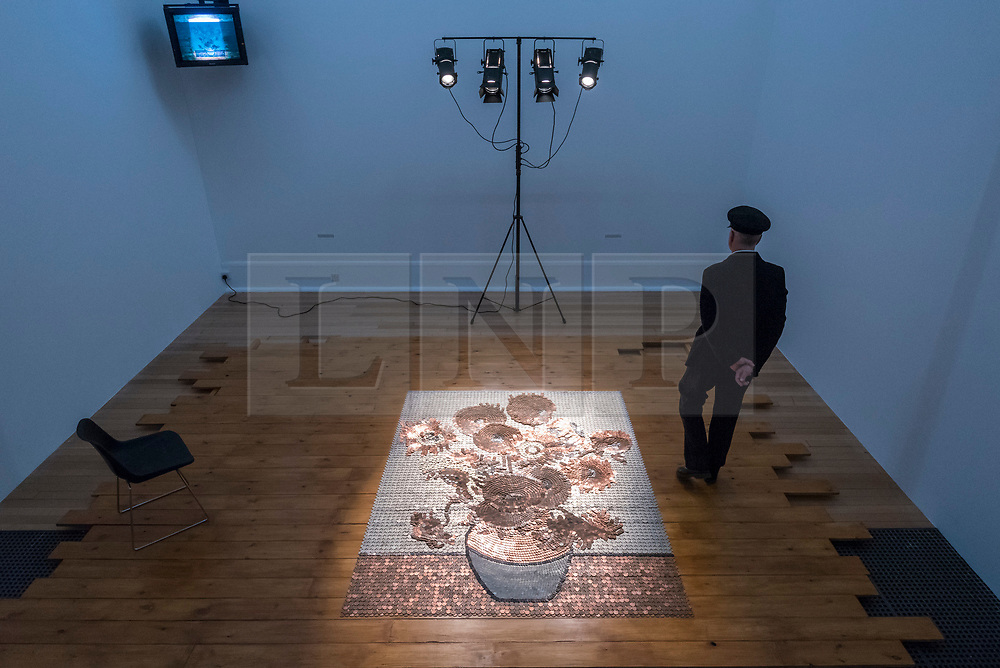 "© Licensed to London News Pictures. 01/04/2019. LONDON, UK.  ""Bureau de Change"", 1987, by Rose Finn-Kelcey is unveiled at Tate Britain.  Coinciding with ""The EY Exhibition:  Van Gogh and Britain"", the live installation consists of 1,000 worth of coins laid out on the floor in the image of Vincent Van Gogh's ""Sunflowers"".  The installation is overseen each day by an actor posing as a security guard, with visitors viewing the scene from a platform and will be in place 1 Aptil to 11 August 2019.  Photo credit: Stephen Chung/LNP"