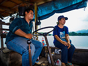 "09 JANUARY 2019 - KANCHANABURI, THAILAND: BOM, the operator of a small ferry on the River Kwai near Kanchanaburi, chats with one of his passengers. The ferry goes across the River Kwai downriver from downtown Kanchanaburi, the site of the famous ""Bridge on the River Kwai."" Small ferries like this, once common on Thai river crossings, are disappearing because Thailand has dramatically improved its infrastructure since this ferry started operating about 50 years ago. The ferry operator said his grandfather started the ferry, with a small raft he would pole across the river, in the late 1960s. Now his family has a metal boat with an inboard engine. There are large vehicle bridges across the river about 5 miles north and south of this ferry crossing, but for people in rural communities on the west side of the river the ferry is still the most convenient way to cross the river.      PHOTO BY JACK KURTZ"