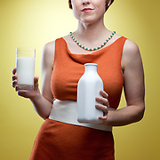 A woman in a 1960s retro dress holds a vintage milk bottle and a glass of milk. Photographed in front of a yellow backdrop with studio lighting.