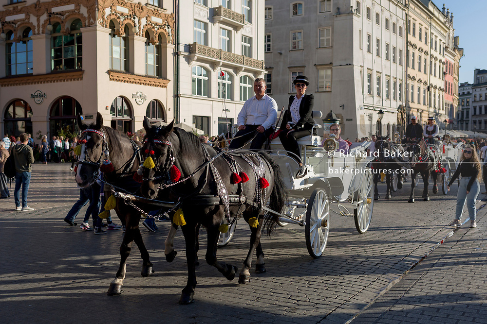 A horse and carriage ride for tourists around Rynek Glowny market square, on 22nd September 2019, in Krakow, Malopolska, Poland.