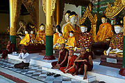 Monks congregate in one of the many surrounding temples of Shwedagon.<br /> <br /> Shwedagon Zedi Daw The, as it is known locally,or The Crown of Burma less formally, is rumoured to be the oldest pagoda in the world dating to 2,600 years old. Standing 99m tall and crowning a hilltop, it can be seen from all over Yangon, by day and night.<br /> <br /> The main gold-plated dome is topped by a stupa containing over 7,000 diamonds, rubies, topaz' and sapphires,all offset by a massive emerald positioned to reflect the setting sun.<br /> <br /> As Myanmar's most revered shrine it has always been customary for families and followers of the Buddha to make the pilgrimage to Shwedagon in the same way that Muslims feel compelled to visit the Kaaba at Mecca, at least once in their lifetime.