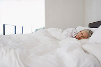 Mature woman lying asleep in bed