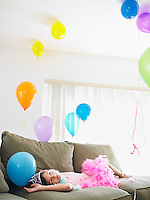 Young girl (7-9) lying on sofa looking at balloons
