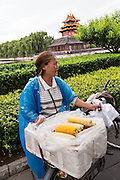 A woman sells corn on the cob near the Arrow Tower on the palace walls of the Forbidden City during a summer evening in Beijing, China