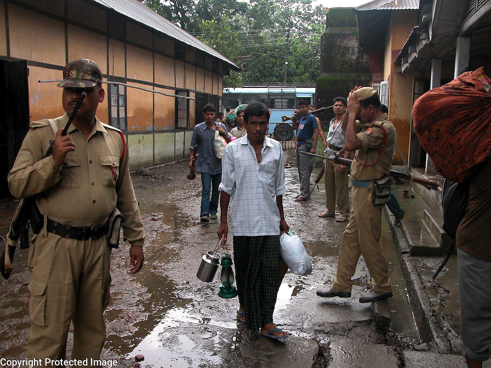 After the floodwaters reduce in the district-jail, the soldiers of the Indian Central Police Force are strictly vigil in the courtyard of the district-jail premises during the hardcore convicts and the extremists are shifting/returning to their own prison cells at Dhubri village, about 298 kilometers  southwest of Gauhati, capital of northeastern Indian state of Assam, Tuesday, July 13, 2004. .Floodwaters of the Asia's one of the largest river, Brahmaputra and its 35 tributaries have affected more than one million in all of Indian subcontinent and disrupted communication in many parts of the India and Bangladesh, sources said. (AP Photo/ Shib Shankar Chatterjee)..