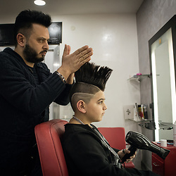 Angelo Ferrara, Luciano's manager, prepares his son's hairstyle inside the beauty salon he runs in Frignano.