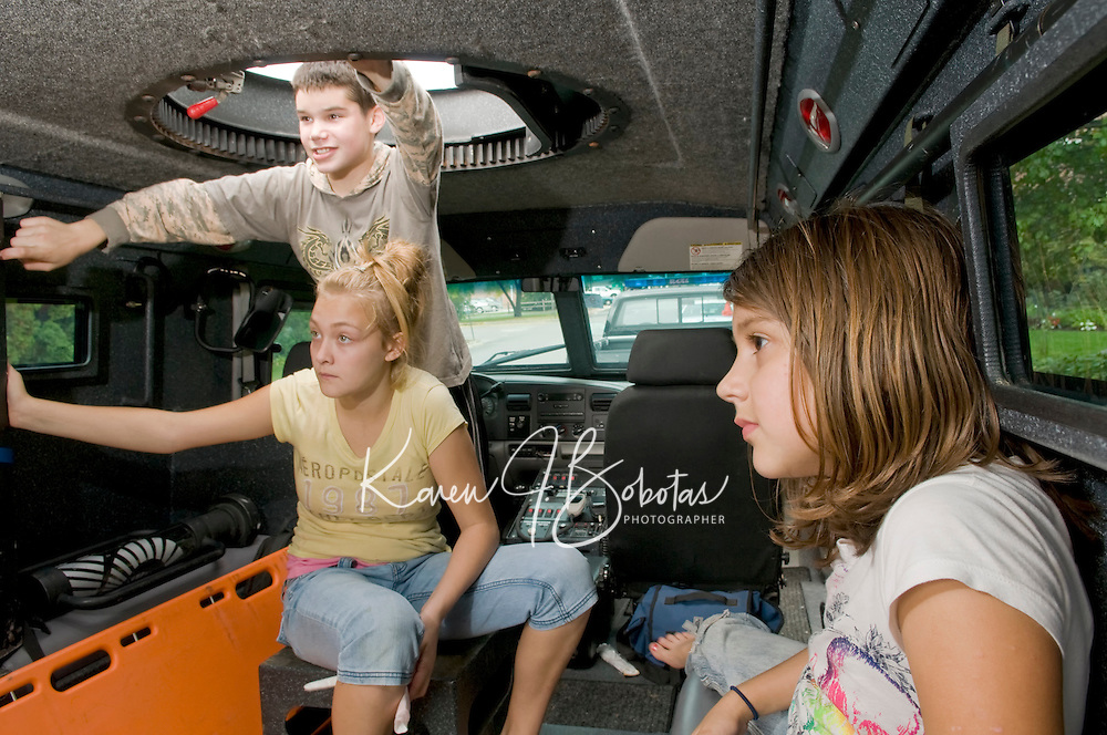 """(l-r) Madison Guyotte, Caitlin McDaniel and Ashley Olisky get a tour from Sgt. Rich Simmons from the Belknap Regional Special Operations Team of their  """"Bearcat"""" SWAT vehicle on display at Laconia Rotary Park on Sunday as part of the Child Safety Day sponsored by the Laconia Rotary Club and Laconia Police and Fire Departments.  (Karen Bobotas/for the Laconia Daily Sun)"""