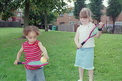 Young boy balancing a ball on a tennis racket,