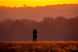 © Licensed to London News Pictures. 05/12/2019. London, UK. A walker capture the rising sun this morning in a frosty and misty Richmond Park as weather forecasters predict warmer weather for the South East. Photo credit: Alex Lentati/LNP