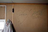"Hal Far, Malta - 21 August, 2012:  A hand drawn heart stating ""Love is life"" appears in one of the 34 containers where migrants live, at the Hal Far Hangar Site in Hal Far, Malta, on 21 August, 2012.<br /> <br /> The Hangar Open Center is a field with an ex-aircraft hangar which, until 2011, included Swiss Red Cross tents in a dark, non lit space in very poor conditions and with inflamable oil on the floor. Today, the hangar is closed and the migrants live in 34 external containers with no water. <br /> <br /> The Open Centres in Malta serve as a temporary accomodation facility, but they ended becoming permanent accomodation centres, except for those immigrants who receive subsidiary protection or refugee status and that are sent to countries such as the United States, Germany, Poland, and others. All immigrants who enter in Malta illegally are detained. Upon arrival to Malta, irregular migrants and asylum seekers are sent to one of three dedicated immigration detention facilities. Once apprehended by the authorities, immigrants remain in detention even after they apply for refugee status. detention lasts as long as it takes for asylum claims to be determined. This usually takes months; asylum seekers often wait five to 10 months for their first interview with the Refugee Commissioner. Asylum seekers may be detained for up to 12 months: at this point, if their claim is still pending, they are released and transferred to an Open Center.<br /> <br /> Gianni Cipriano for The New York Times"