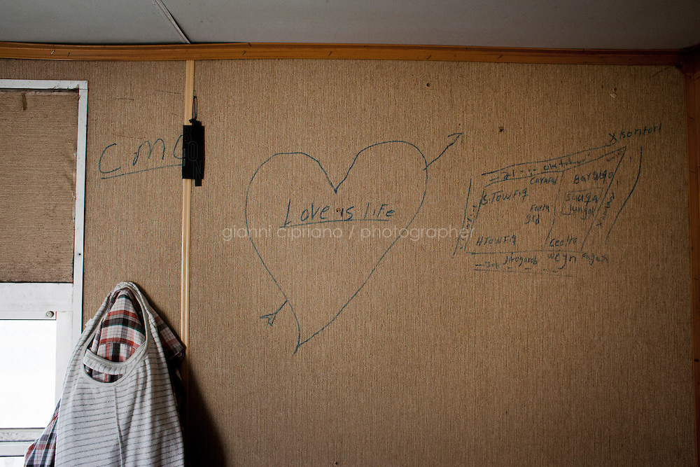 Hal Far, Malta - 21 August, 2012:  A hand drawn heart stating &quot;Love is life&quot; appears in one of the 34 containers where migrants live, at the Hal Far Hangar Site in Hal Far, Malta, on 21 August, 2012.<br /> <br /> The Hangar Open Center is a field with an ex-aircraft hangar which, until 2011, included Swiss Red Cross tents in a dark, non lit space in very poor conditions and with inflamable oil on the floor. Today, the hangar is closed and the migrants live in 34 external containers with no water. <br /> <br /> The Open Centres in Malta serve as a temporary accomodation facility, but they ended becoming permanent accomodation centres, except for those immigrants who receive subsidiary protection or refugee status and that are sent to countries such as the United States, Germany, Poland, and others. All immigrants who enter in Malta illegally are detained. Upon arrival to Malta, irregular migrants and asylum seekers are sent to one of three dedicated immigration detention facilities. Once apprehended by the authorities, immigrants remain in detention even after they apply for refugee status. detention lasts as long as it takes for asylum claims to be determined. This usually takes months; asylum seekers often wait five to 10 months for their first interview with the Refugee Commissioner. Asylum seekers may be detained for up to 12 months: at this point, if their claim is still pending, they are released and transferred to an Open Center.<br /> <br /> Gianni Cipriano for The New York Times