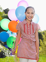Portrait of girl (10-12) with bunch of balloons smiling