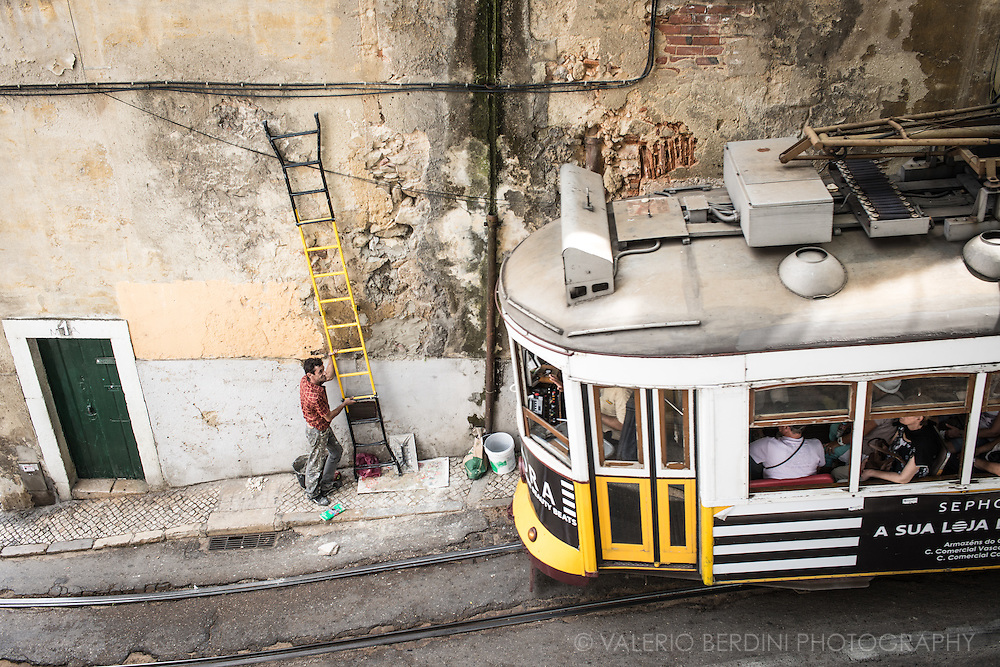 A man had to get off a ladder and take a break from his job to let the tram pass in one of Lisbon narrow streets.