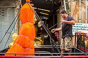 """12 NOVEMBER 2012 - BANGKOK, THAILAND:   A truck driver secures a statue of the Buddha to his truck on Bamrung Muang Street in Bangkok. Buddhas are covered in saffron when they are moved. Thanon Bamrung Muang (Thanon is Thai for Road or Street) is Bangkok's """"Street of Many Buddhas."""" Like many ancient cities, Bangkok was once a city of artisan's neighborhoods and Bamrung Muang Road, near Bangkok's present day city hall, was once the street where all the country's Buddha statues were made. Now they made in factories on the edge of Bangkok, but Bamrung Muang Road is still where the statues are sold. Once an elephant trail, it was one of the first streets paved in Bangkok. It is the largest center of Buddhist supplies in Thailand. Not just statues but also monk's robes, candles, alms bowls, and pre-configured alms baskets are for sale along both sides of the street.    PHOTO BY JACK KURTZ"""