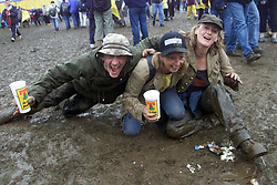 Fans L-R TREVOR COTTERILL, MAGGIE MCILVARY & TRACY LEE have fun at a muddy T in the Park festival site..T in the Park music festival, held at Balado, Kinross in Fife, Scotland, on the weekend of Saturday 8 July and Sunday 9 July 2000..