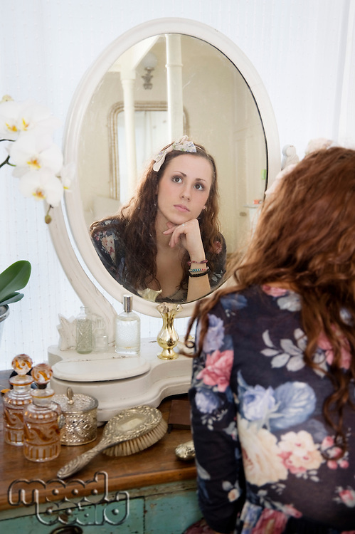 Young woman thinking in front of mirror