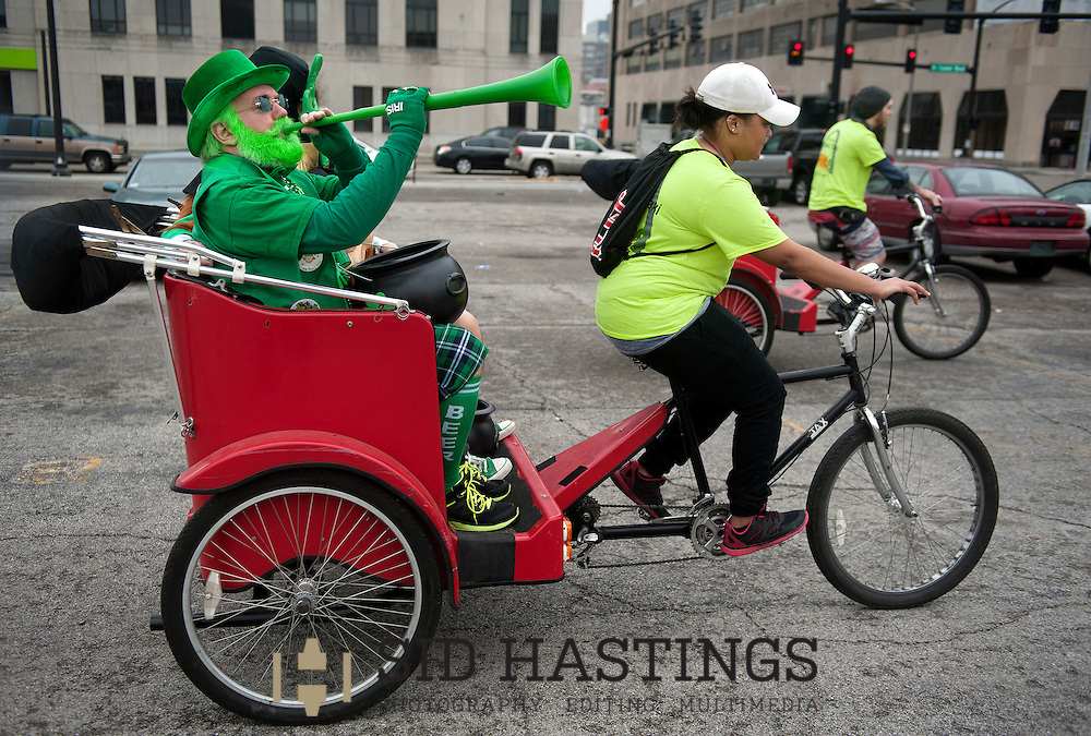 12 MARCH 2016 -- ST. LOUIS -- St. Patrick's Day parade-goers Steve Cummins (left) and Dan Trtanj (partially obscured) ride a pedicab operated by St. Louis 3Wheel Taxi pedicab driver Lolita Murray (center)  during the downtown St. Patrick's Day parade Saturday, March 12, 2016. Murray and fellow driver Tim Burdin (right) spent the day ferrying parade-goers from their cars to the parade route. Photo © copyright 2015 Sid Hastings.