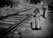 Untouchable (Dalit) girl from squatter family, that earns food money from rag 'recycling', plays in rail yard, Delhi, India.